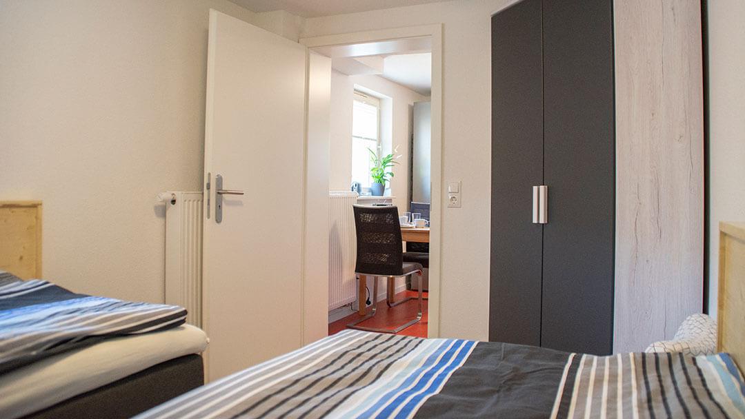 Blick aus dem Schlafzimmer mit Kleiderschrank in Richtung Wohnraum