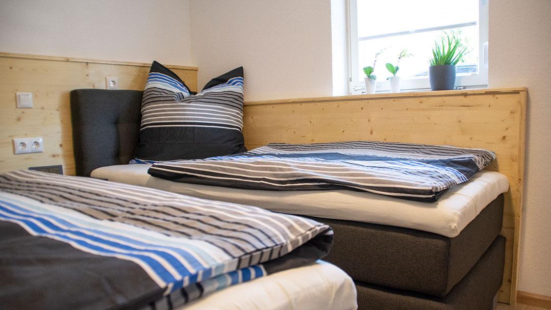 Dunkelgraues Einzelbett mit grau-blauer Bettwäsche bezogen