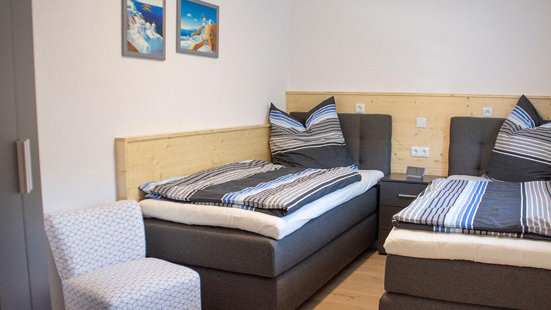Zwei dunkelgraue Einzelbetten mit grau-blauer Bettwäsche bezogen