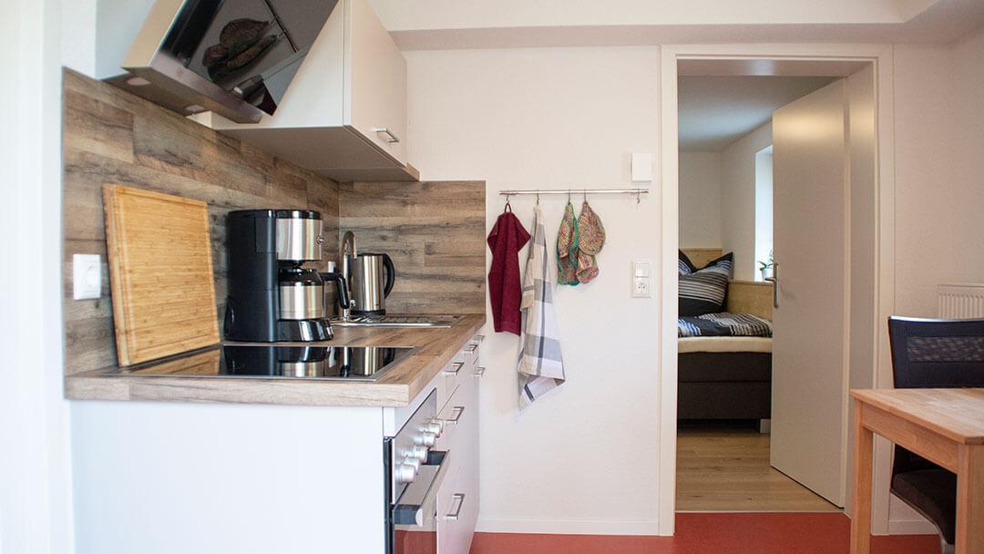 Wohnraum mit Küchenzeile und Esstisch und Blick in das Schlafzimmer
