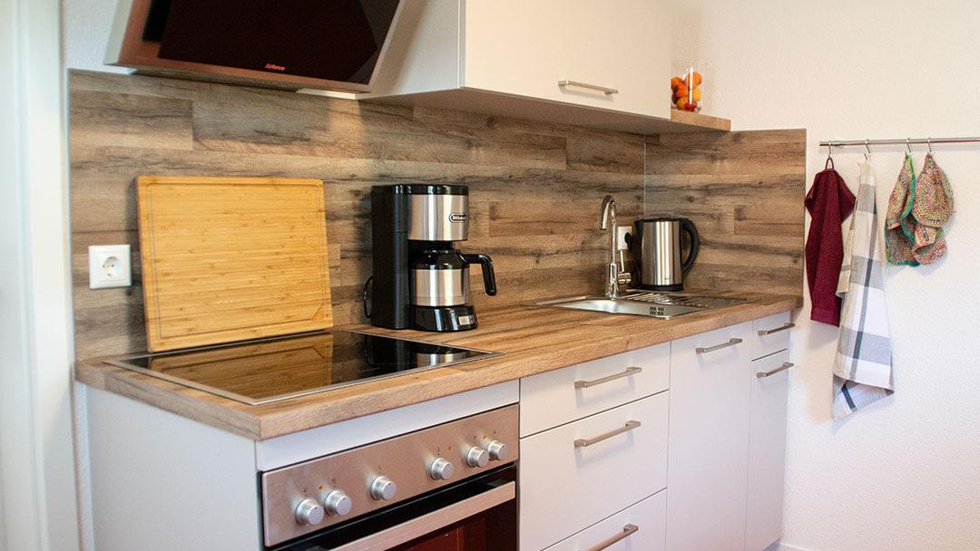 Küchenzeile mit weißer Front und einer Arbeitsplatte aus Holz