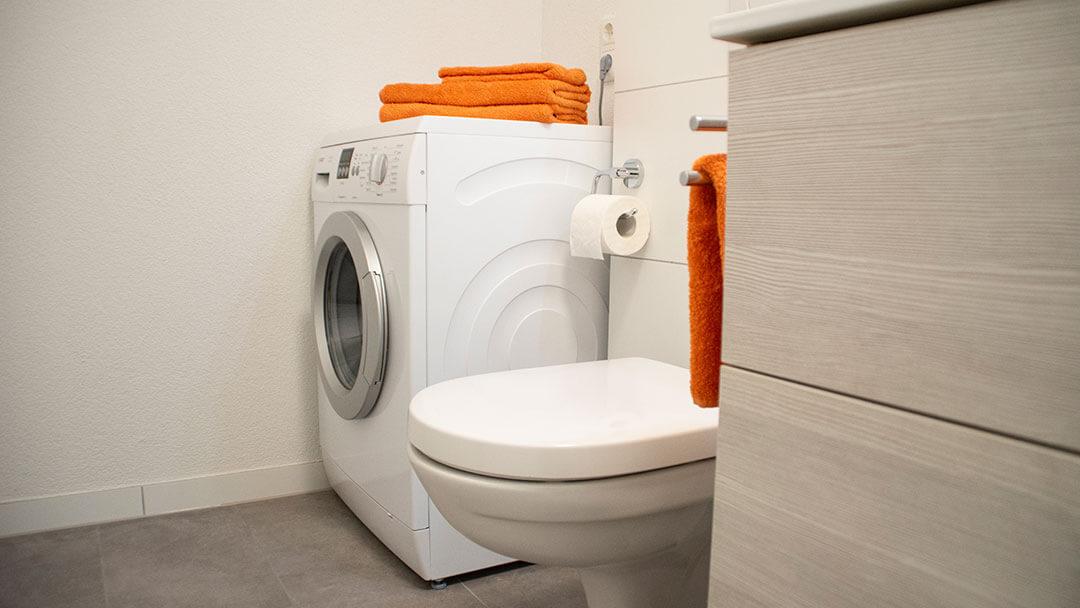 Waschmaschine im Badezimmer links neben dem WC