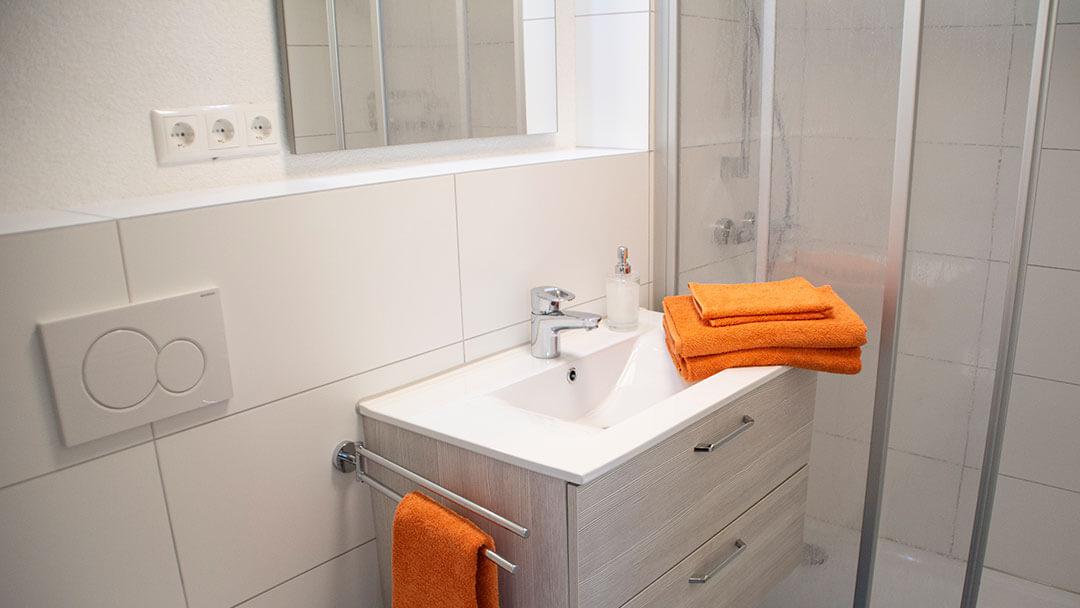 Orangene Handtücher auf dem Waschtisch im Badezimmer